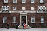 出産した第3子の王子を抱っこし退院する英王室のキャサリン妃(中央右)とウィリアム王子(同左)=ロンドンで2018年4月23日、ロイター
