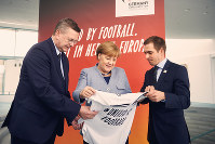 In this March 26, 2018 file photo German chancellor Angela Merkel, center, German Football Federation head, Reinhard Grindel, left, and former soccer player Philipp Lahm, right, promote the European Soccer Championship 2024 in Berlin. (Felix Zahn/dpa via AP)