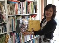 無料で貸し出している点字付き絵本を手にする大下利栄子さん=神奈川県葉山町で