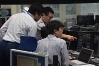 小惑星探査機「はやぶさ2」の着陸訓練で、意見を交わすJAXAの職員ら=相模原市中央区のJAXA相模原キャンパスで2018年4月24日、池田知広撮影