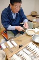 糸を使って穂からのりを絞り出す仕上げ作業をする松谷文夫さん=奈良市南新町のあかしやで、大川泰弘撮影