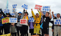 Protesters chant slogans opposing the relocation of U.S. Marine Corps Air Station Futenma near the seawall construction site in the Henoko district of Nago, Okinawa Prefecture, on April 25, 2018. (Mainichi)