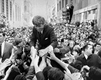 In this April 2, 1968 file photo, U.S. Sen. Robert F. Kennedy, D-NY, shakes hands with people in a crowd while campaigning for the Democratic party's presidential nomination on a street corner in Philadelphia. (AP Photo/Warren Winterbottom, File)