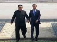 握手する北朝鮮の金正恩朝鮮労働党委員長(左)と、韓国の文在寅大統領=AP