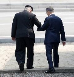 北朝鮮の金正恩朝鮮労働党委員長(左)に促され、軍事境界線を越える韓国の文在寅大統領=AP