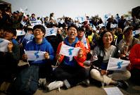 「統一旗」を掲げて南北首脳会談の中継を見つめる人々=韓国北部・坡州で27日、ロイター