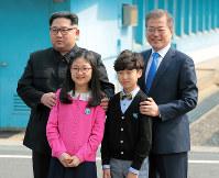 韓国側の板門店近くの小学校に通う子どもたちと記念撮影する金委員長(左)と文大統領=韓国・板門店で27日、韓国共同写真記者団・ロイター