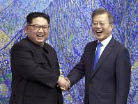 笑顔で握手し、写真撮影に応じる金正恩朝鮮労働党委員長(左)と文在寅韓国大統領=韓国・板門店「平和の家」で2018年4月27日、韓国共同写真記者団・AP