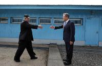 軍事境界線を挟んで握手する北朝鮮の金正恩朝鮮労働党委員長(左)と韓国の文在寅大統領=板門店で2018年4月27日、韓国共同写真記者団