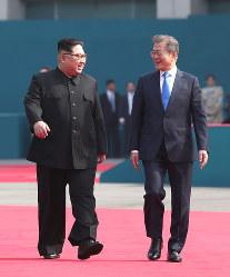 談笑しながら首脳会談の会場に向かう北朝鮮の金正恩朝鮮労働党委員長(左)と韓国の文在寅大統領=板門店で2018年4月27日、韓国共同写真記者団