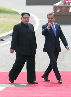 首脳会談の会場に向かう北朝鮮の金正恩朝鮮労働党委員長(左)と韓国の文在寅大統領=韓国・板門店で2018年4月27日、韓国共同写真記者団
