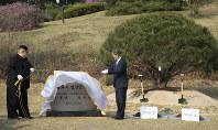 そろって植樹し、碑を除幕する北朝鮮の金正恩朝鮮労働党委員長(左)と韓国の文在寅大統領=板門店で2018年4月27日、韓国共同写真記者団