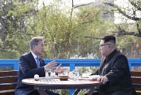 テラスで話す北朝鮮の金正恩朝鮮労働党委員長(右)と韓国の文在寅大統領=板門店で2018年4月27日、韓国共同写真記者団