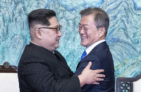 板門店宣言に署名後、抱き合う北朝鮮の金正恩朝鮮労働党委員長(左)と韓国の文在寅大統領=韓国・板門店で2018年4月27日、韓国共同写真記者団