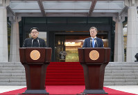 共同発表する北朝鮮の金正恩朝鮮労働党委員長(左)と韓国の文在寅大統領=板門店で2018年4月27日、韓国共同写真記者団