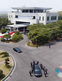 厳重に警護された北朝鮮の金正恩朝鮮労働党委員長が乗る車(手前)。奥は韓国側施設=板門店で2018年4月27日、韓国共同写真記者団