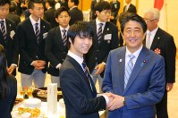 Figure skating superstar Yuzuru Hanyu, left, shakes hands with Prime Minister Shinzo Abe after a ceremony awarding 95 medalists and high-ranking performers at the Pyeongchang Olympics and Paralympics with letters of appreciation, at the prime minister's office on April 26, 2018. (Mainichi)