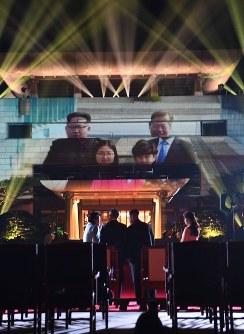 映像を見ながら言葉を交わす韓国の文在寅大統領(中央左)と北朝鮮の金正恩朝鮮労働党委員長(同右)=板門店で2018年4月27日、韓国共同写真記者団