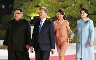 公演会場に向かって並んで歩く(左から)北朝鮮の金正恩朝鮮労働党委員長、韓国の文在寅大統領、李雪主夫人、金正淑夫人=板門店で2018年4月27日、韓国共同写真記者団