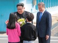 子供たちから花束を受け取る北朝鮮の金正恩朝鮮労働党委員長(左)と韓国の文在寅大統領=韓国・板門店で2018年4月27日、韓国共同写真記者団