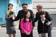 子供たちとの記念撮影に臨む北朝鮮の金正恩朝鮮労働党委員長(中央)と韓国の文在寅大統領(右)。左は金与正党第1副部長=韓国・板門店で2018年4月27日、韓国共同写真記者団