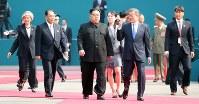 首脳会談の会場に向かう北朝鮮の金正恩朝鮮労働党委員長(中央左)と韓国の文在寅大統領(同右)。同奥は金与正党第1副部長=韓国・板門店で2018年4月27日、韓国共同写真記者団