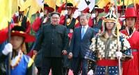 首脳会談の会場に談笑しながら向かう北朝鮮の金正恩朝鮮労働党委員長(左)と韓国の文在寅大統領=韓国・板門店で2018年4月27日、韓国共同写真記者団