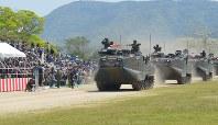 詰めかけた大勢の市民の前を進む水陸両用車=長崎県佐世保市の陸上自衛隊相浦駐屯地で2018年4月28日、綿貫洋撮影