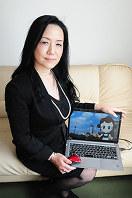 スマートアバターを表示したパソコンを持ちながら「伝えることにこだわり、人の絆を創造していきたい」と話すBONDの古川社長=北九州市小倉北区で