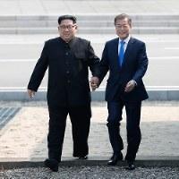 手を取り合って軍事境界線を越える北朝鮮の金正恩朝鮮労働党委員長(左)韓国の文在寅大統領=韓国・板門店で4月27日、韓国共同写真記者団