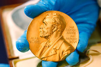 In this file photo dated April 17, 2015, a national library employee shows the gold Nobel Prize medal awarded to the late novelist Gabriel Garcia Marquez, in Bogota, Colombia. (AP Photo/Fernando Vergara)