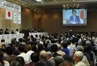 改憲派憲法集会の冒頭に映された安倍首相のビデオメッセージを見る参加者たち=東京都千代田区で2018年5月3日午後1時38分、根岸基弘撮影