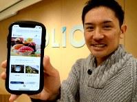フォリオの甲斐CEOが手にするスマホの画面には、「寿司」など、投資の堅苦しいイメージを覆すユニークなテーマが並ぶ=東京都内で、岡大介撮影