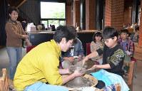 高井晴美さん(左端)らの見守る中、ろくろで茶わんを仕上げる小学生(手前右)=京都府舞鶴市北吸の舞鶴赤れんがパークで、鈴木健太郎撮影