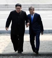 手を取り合って軍事境界線を越える北朝鮮の金正恩朝鮮労働党委員長(左)韓国の文在寅大統領=板門店で4月27日、韓国共同写真記者団