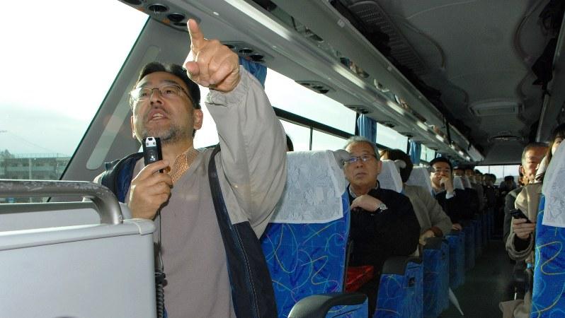 ツアーのバスで一番前の席に座り解説を行う藻谷浩介さん