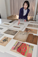 Kyoto University Graduate School of Letters professor Kazuko Tanaka shows off the replications of the Hedin sketches created by art school students that she discovered inside a yellowed envelope, center right, in Kyoto's Sakyo Ward, on April 26, 2018. (Mainichi)