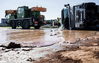 Caption Tons of liquid milk chocolate are spilled and block six lanes on a highway after a truck transporting it overturned near Slupca, in western Poland, on May 9, 2018. (AP Photo)