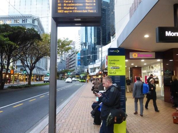 都心で帰宅のバスを待つ通勤者。街は小さいが公共交通網は充実している