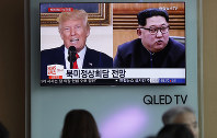 People watch a TV screen showing file footage of U.S. President Donald Trump, left, and North Korean leader Kim Jong Un, right, during a news program at the Seoul Railway Station in Seoul, South Korea, on May 11, 2018. (AP Photo/Lee Jin-man)