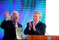 米国の在イスラエル大使館移転を祝うイスラエル政府の式典で、米国のフリードマン駐イスラエル大使(左)に拍手を送るネタニヤフ首相=エルサレムのイスラエル外務省で13日、ロイター