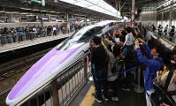 People take photos as West Japan Railway Co.'s 500 Type Eva Shinkansen bullet train leaves on its final journey from JR Shin-Osaka Station in Osaka on May 13, 2018. (Mainichi)