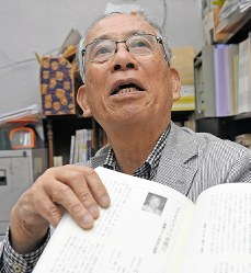 Mitsugi Moriguchi holds a copy of the Nagasaki no shogen no kai (Nagasaki testimonials association)'s