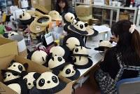 出荷前に検品されるジャイアントパンダを模した麦わら帽子=埼玉県春日部市の「田中帽子店」で2018年5月11日、西本勝撮影