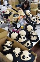 出荷前に検品されるジャイアントパンダを模した麦わら帽子=埼玉県春日部市の「田中帽子店」で2018年5月11日、西本