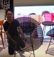 カルテルの新作椅子を傾けて見せる吉岡徳仁さん=2018年4月17日、永田晶子撮影