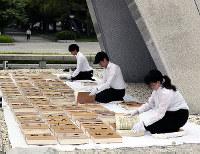 原爆慰霊碑の前に原爆死没者名簿を並べ、「風通し」をする広島市職員=広島市中区の平和記念公園で2018年5月16日午前9時、幾島健太郎撮影
