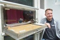 ドイツで最初にできたゆりかご「ベビークラッペ」について説明するとハネス・ゲルトナーさん=ドイツ北部のハンブルクで