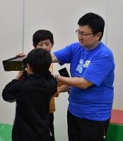 子どもたちにVRゴーグルの説明をする板宮朋基教授(右)=愛知県豊田市で2018年5月13日午後3時9分、三浦研吾撮影