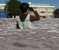 箱に装着したスマートフォンで校庭が水に漬かったAR映像を見て、被害を疑似体験する子ども=東京都三鷹市立第七小で、板宮朋基教授提供